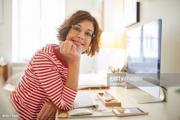 portrait of content mature woman sitting at desk at home - 40 44 jaar stockfoto's en -beelden