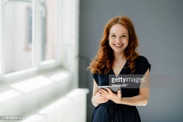 portrait of content redheaded businesswoman with digital tablet in a loft - rotes haar stock-fotos und bilder