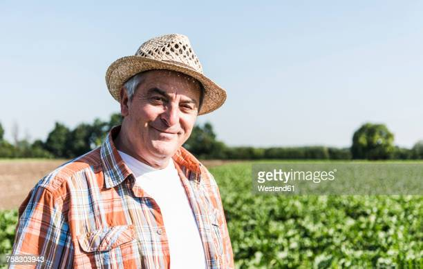 portrait of content senior farmer standing in front of a field - straw hat stock pictures, royalty-free photos & images