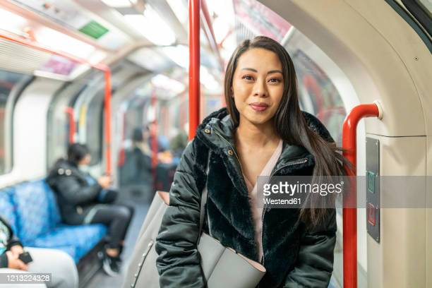 portrait of content woman in underground train, london, uk - london underground stock pictures, royalty-free photos & images