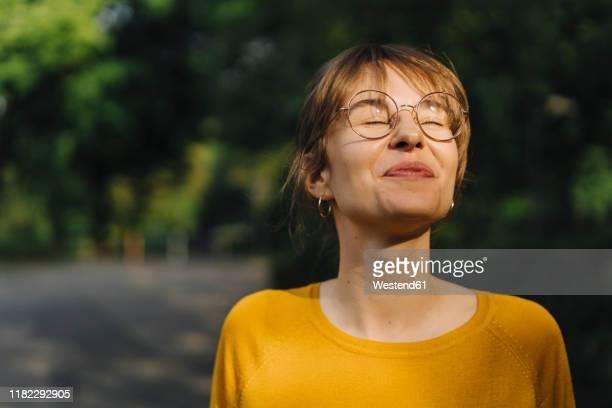 portrait of content young woman with closed eyes - alles hinter sich lassen stock-fotos und bilder