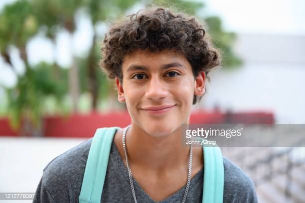 portrait of contented male hispanic teenager - v neck stock pictures, royalty-free photos & images
