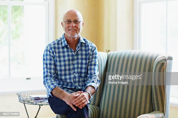portrait of contented senior man at home - 65 69 ans photos et images de collection