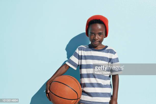 portrait of cool boy holding basketball, on studio background - esporte - fotografias e filmes do acervo