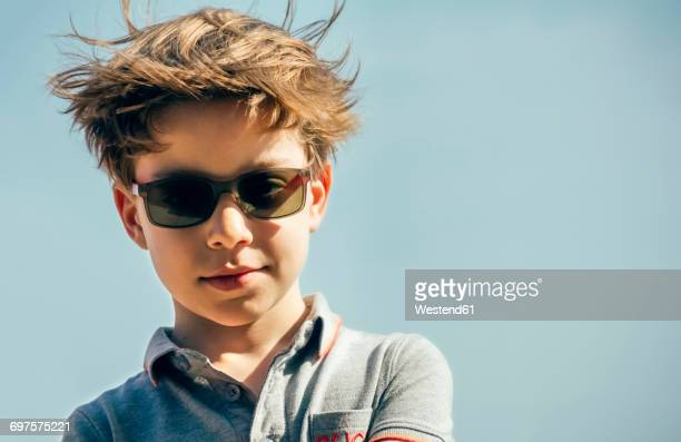 Portrait of cool boy with sunglasses and blowing hair in front of sky