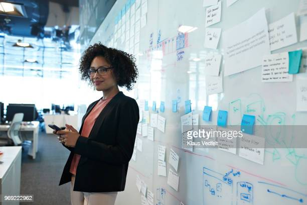 portrait of cool businesswoman holding smartphone - premium access stock pictures, royalty-free photos & images