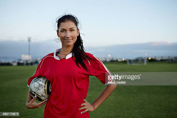 Portrait of cool female soccer player holding ball