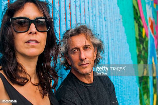 Portrait of cool mature couple in front of graffiti wall
