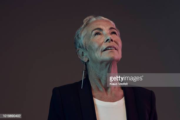 portrait of cool mature woman looking up, with coloured lights - black blazer stock photos and pictures