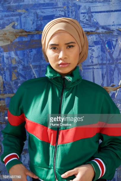 Portrait of cool muslim woman against blue background