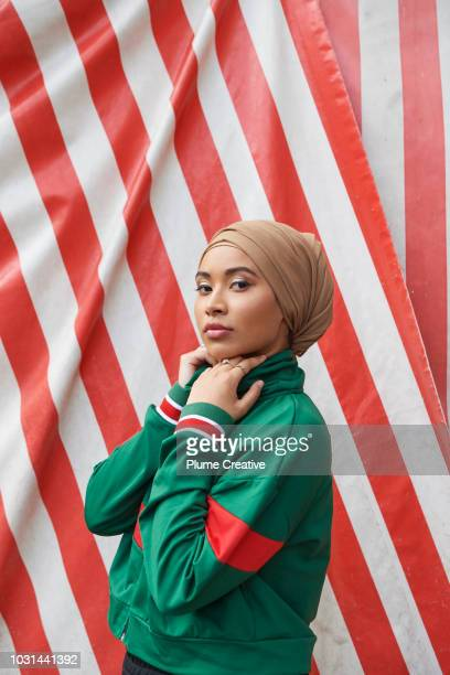 Portrait of cool muslim woman against striped background