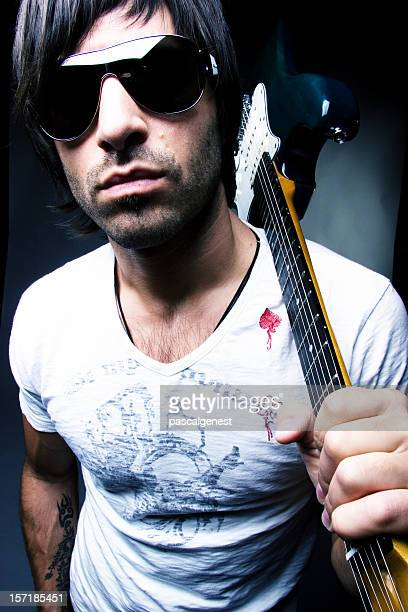 Portrait of cool rock star with sunglasses holding guitar