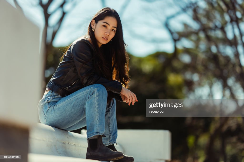 Portrait of cool young and beautiful woman sitting in park and looking at camera : Stock Photo