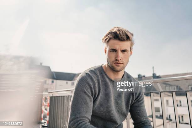 portrait of cool young man sitting on balcony - one young man only stock-fotos und bilder