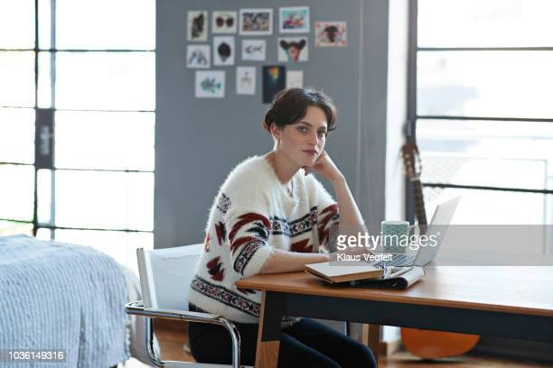 portrait of cool young woman sitting in apartment with laptop - 毅然とした ストックフォトと画像