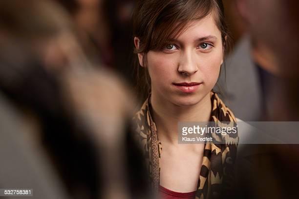 Portrait of cool young woman standing in crowd