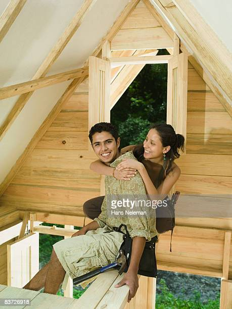 Portrait of couple building home in forest