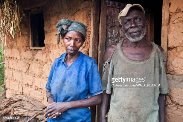 Portrait of couple by mud hut, Masango, Cibitoke, Burundi, Africa