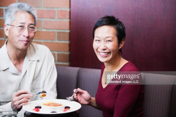 Portrait of couple eating in restaurant
