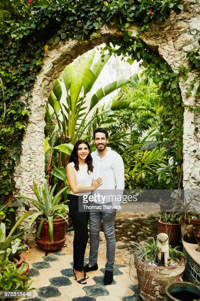 Portrait of couple embracing in backyard garden during dinner party