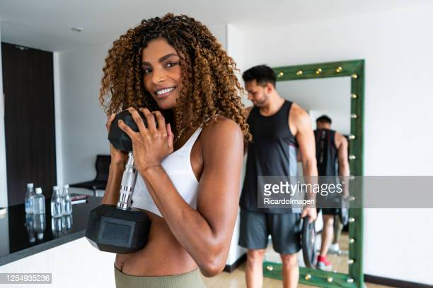 portrait of couple exercising at home through covid-19 quarantine - musculoso stock pictures, royalty-free photos & images