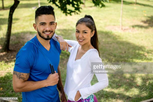 Portrait of couple exercising at the park using a jumping rope