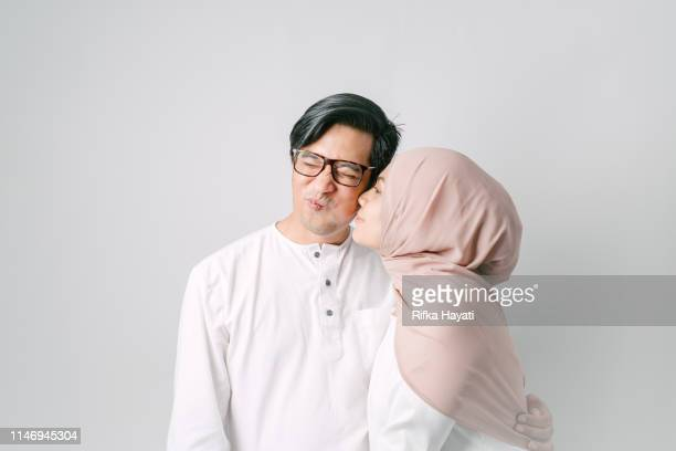 portrait of couple for hari raya aidilfitri (eid al-fitr) - muslim couple stock pictures, royalty-free photos & images