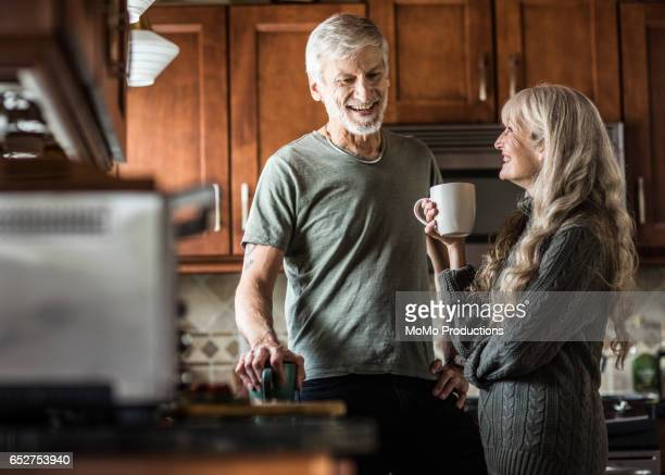 portrait of couple (60yrs) having coffee in kitchen - 60 69 years stock pictures, royalty-free photos & images