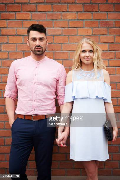 Portrait of couple holding hands in front of brick wall