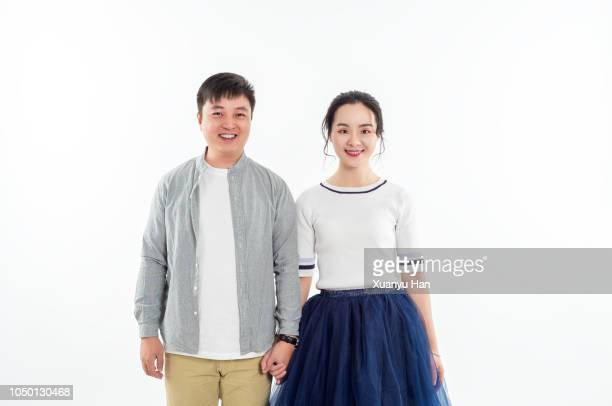portrait of couple holding hands while standing against white background - 隣り合わせ ストックフォトと画像