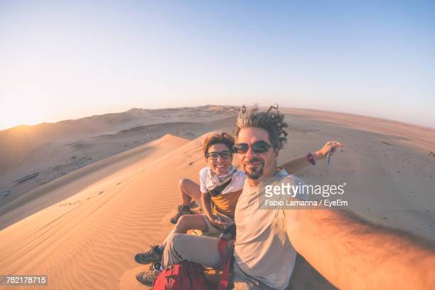 Portrait Of Couple In Desert Against Clear Sky