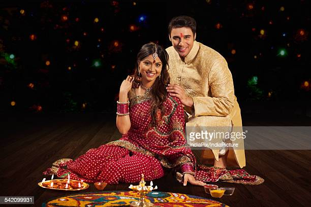 Portrait of couple in front of rangoli