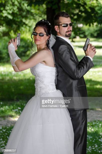Portrait Of Couple In Wedding Dress Holding Guns While Standing Back To Back At Park