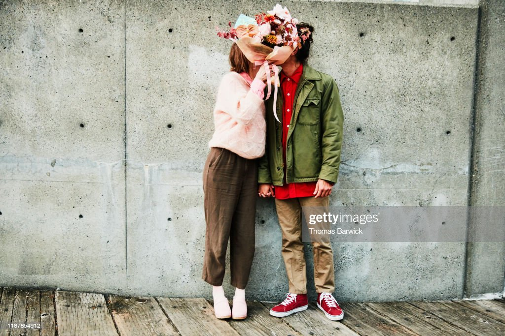 Portrait of couple kissing while hidden behind bouquet of flowers : Stock-Foto