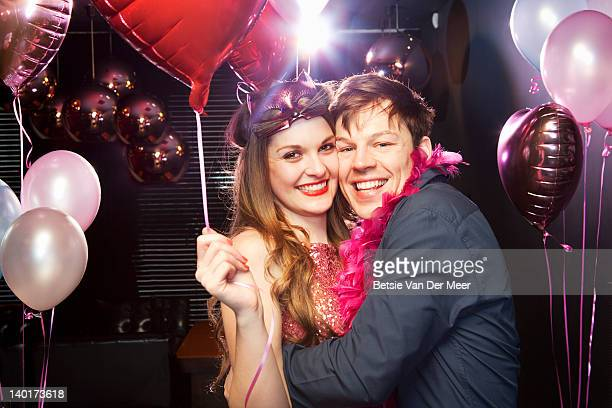 Portrait of couple laughing at party.