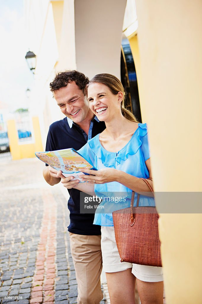 Portrait of couple looking at guidebook : Bildbanksbilder