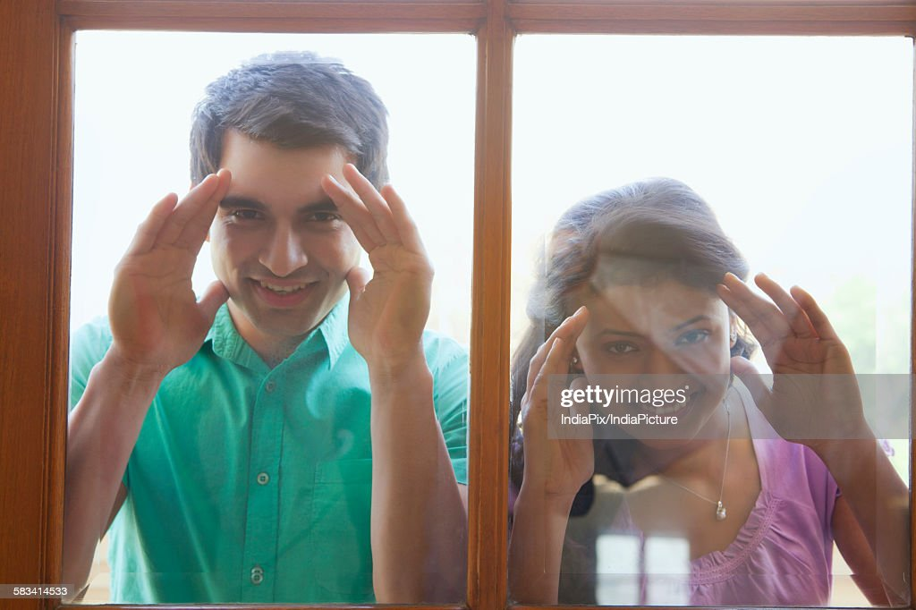 Portrait of couple looking inside new house : Stock Photo