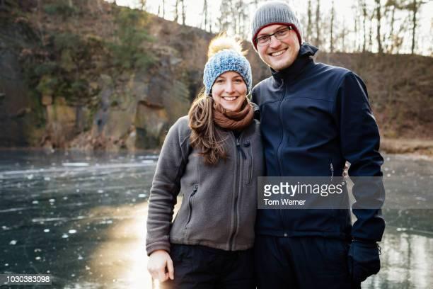 portrait of couple on frozen lake - kopfbedeckung stock-fotos und bilder