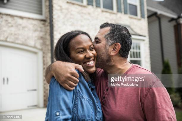 portrait of couple out front of new home - kissing stock pictures, royalty-free photos & images