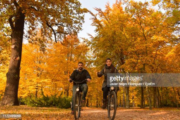 portrait of couple riding bicycles in park during autumn - charlottenburg palace stock pictures, royalty-free photos & images