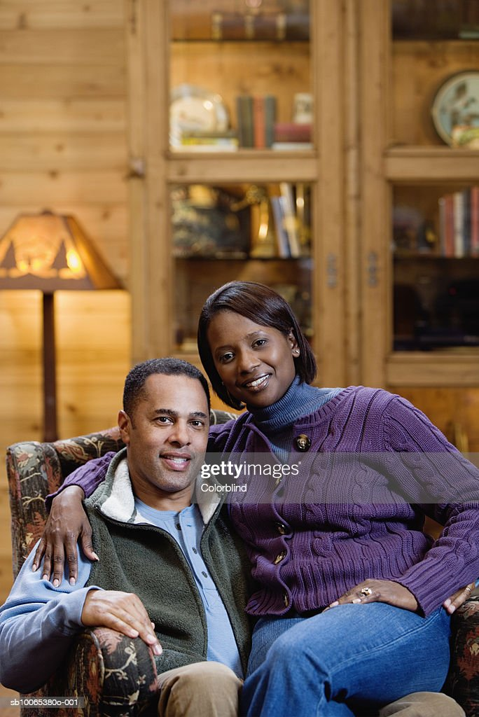 Portrait of couple sitting in armchair, smiling : Foto stock