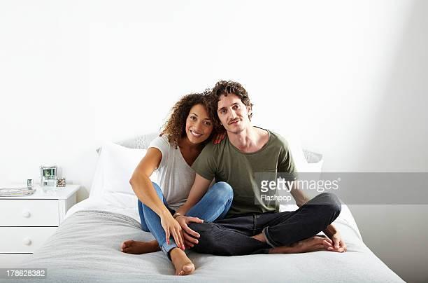 portrait of couple sitting on bed together - gemengde afkomst stockfoto's en -beelden