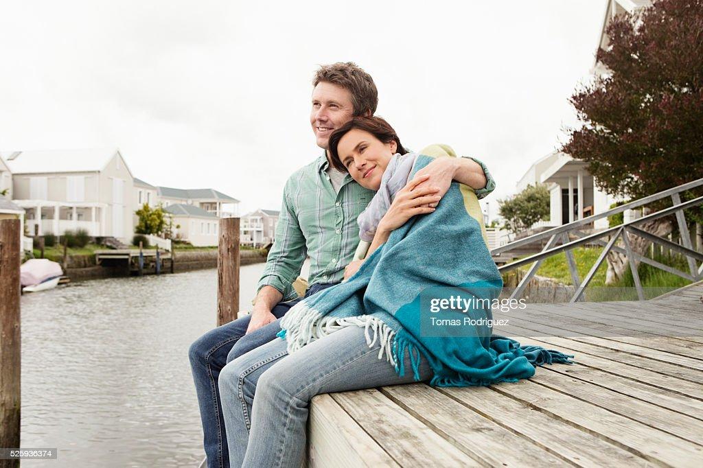 Portrait of couple sitting on pier relaxing : Foto de stock