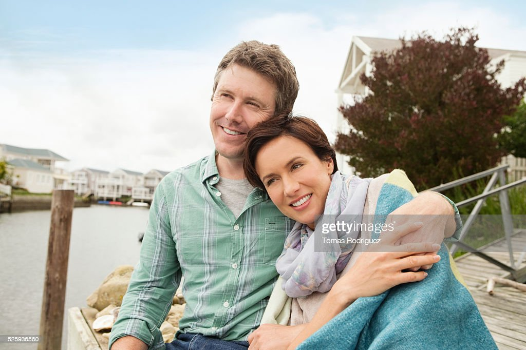 Portrait of couple sitting on pier relaxing : Photo