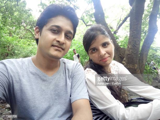 Portrait Of Couple Standing Against Trees At Forest