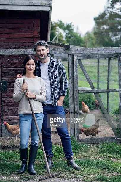 Portrait of couple standing at poultry farm