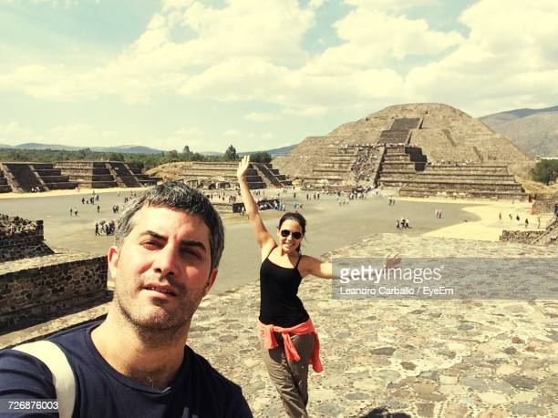 Portrait Of Couple Standing At Pyramid Of The Moon Against Cloudy Sky