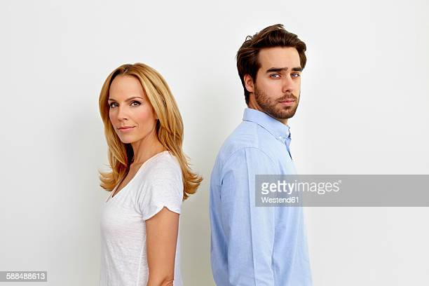 Portrait of couple standing back to back in front of white background