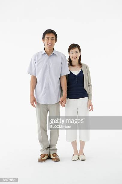 Portrait of couple standing hand in hand, studio shot