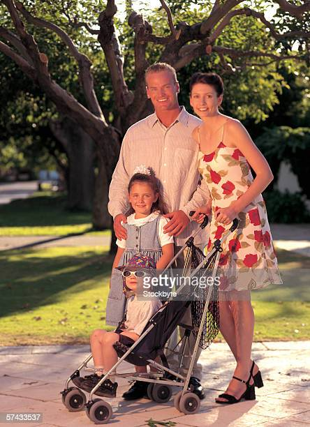 portrait of couple standing with their children outside